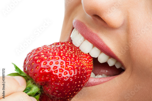 Fotografering  Extreme close up of teeth biting strawberry.
