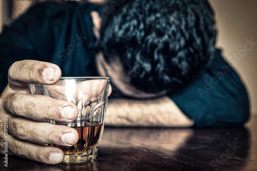 Foto op Plexiglas Bar Drunk man holding a drink and sleeping on a table