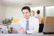 Confident businessman sitting behind the desk