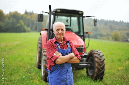 Fotografia Proud farmer standing in front of his red tractor