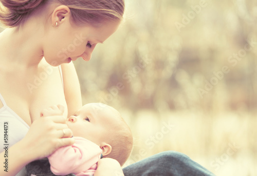 Photo  mother feeding her baby in nature outdoors in the park