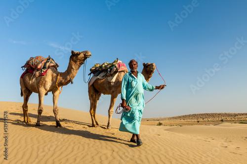 Fotografering  Cameleer (camel driver) with camels in dunes of Thar desert. Raj