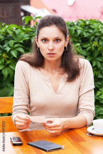 Fotografie, Obraz  Девушка в кафе в шоке от суммы счета