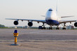 Big jetplane parked at airport, focus on ground lamp at taxiway