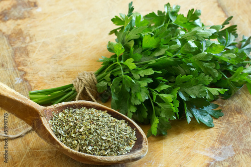 Fotografía  Fresh  and dry parsley on wooden background