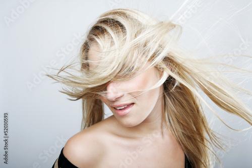 Valokuva Playful blond woman flicking her hair