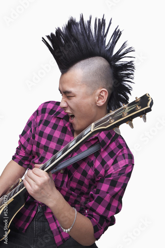 Photo  Young man with punk Mohawk playing guitar