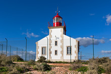 Bright Lighthouse Beyond Chain Link Fence