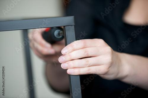 Fotografie, Tablou  Hands screw together a piece of furniture