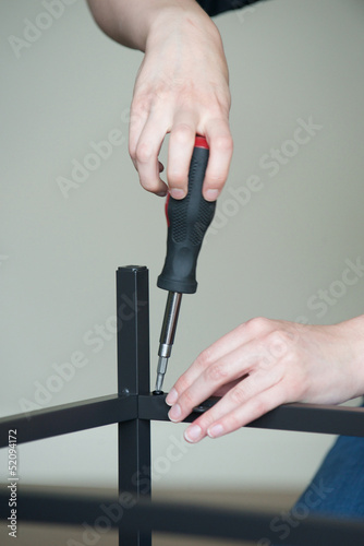 Fotografie, Tablou  Vertical of hands screw together a piece of furniture, no body