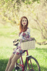 FototapetaGirl on a bike in the countryside