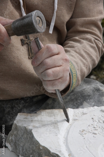Fotografía  stonemason with ancient costume during the processing of the sto