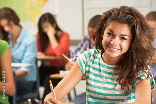 Obraz Portrait Of Female Pupil Studying At Desk In Classroom - fototapety do salonu
