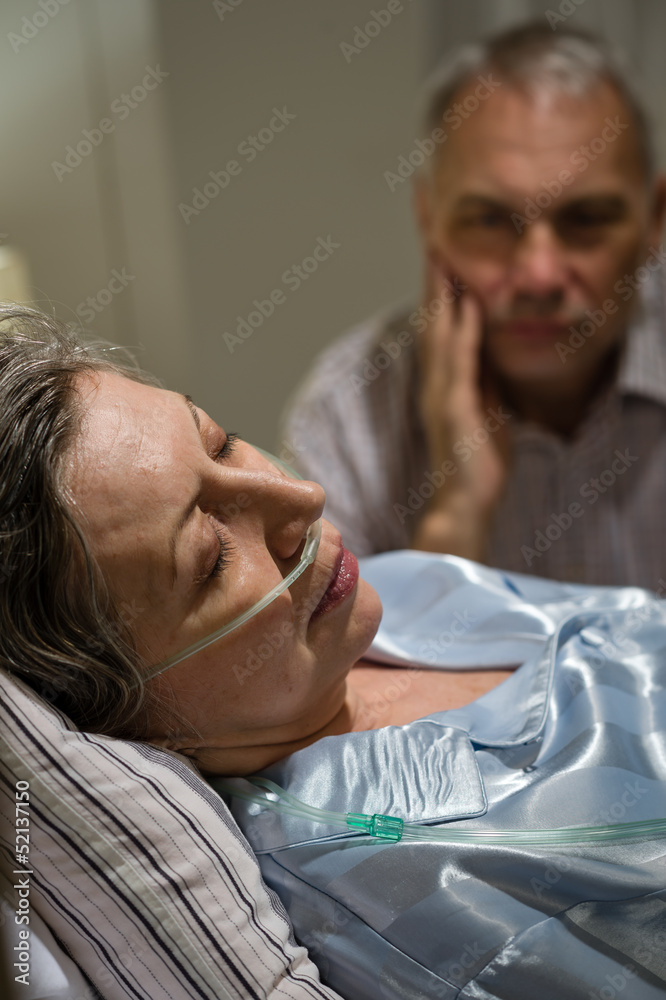 Fototapeta Dying woman in bed with caring man