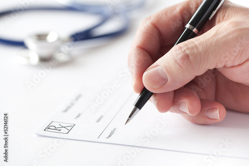 Fotografie, Obraz  Doctor writing a prescription on Rx form in the consulting room