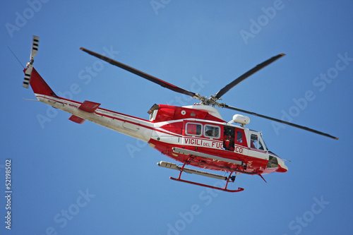 Poster Helicopter patrol helicopter of firefighters in blue sky over a fire 4