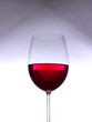 Glass with red wine on gray-white gradient background