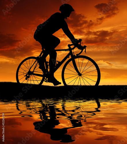 silhouette of the cyclist riding a road bike at sunset - 52267214