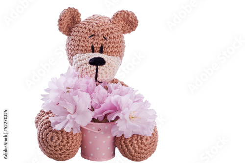 brown stuffed animal teddy bear with pink blossom in a bucket