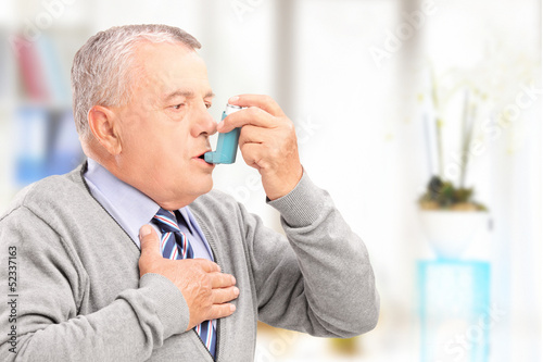 Obraz na plátně Mature man treating asthma with inhaler