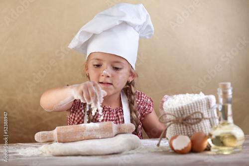 mala-dziewczynka-w-czapce-kucharza-walkujaca-ciasto