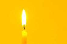 Burning Candle On Yellow Backg...