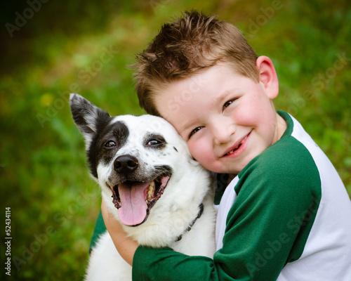 Photo  Child lovingly embraces his pet dog, a blue heeler