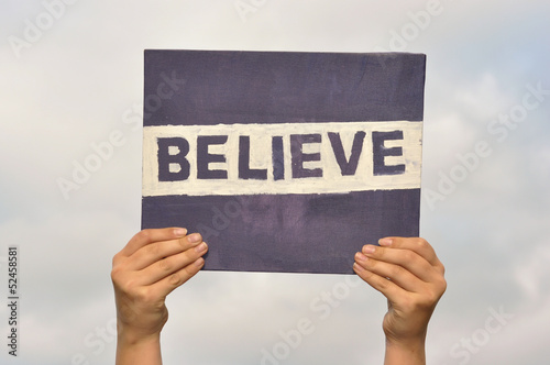 Hand holding up a self painted text Believe against clouds Poster