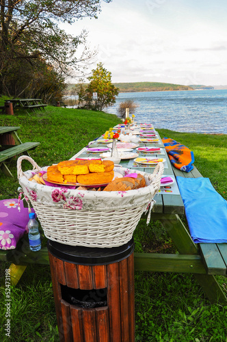 Foto op Aluminium Picknick picnic table on grass by lake