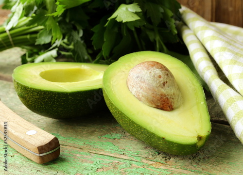 ripe avocado cut in half on a wooden table Wallpaper Mural