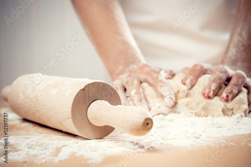 Fotografie, Obraz  Woman kneading dough, close-up photo