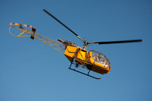 Flying Yellow Helicopter On Blue Sky