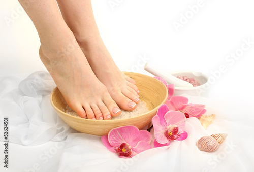 Poster Pedicure Female feet in spa bowl with sea salt, isolated on white