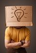 Young man gesturing with a cardboard box on his head with light
