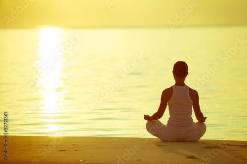 Caucasian woman practicing yoga at seashore - 52721361