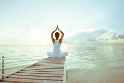 Foto op Canvas Ontspanning Caucasian woman practicing yoga at seashore