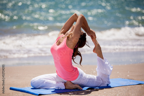 Pretty young brunette practicing some yoga at the beach - 52724283