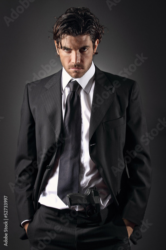 Attractive and elegant man posing with a gun in his trousers Poster