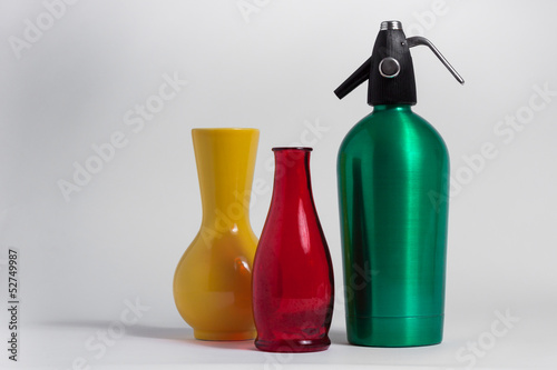 Fotografía  Still life of red bottle yellow vase and green seltzer siphon