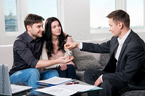 Photo  Happy couple with real estate agent