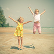 flying jump beach two girls on blue sea shore in summer vacation