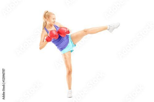 Photo  Female with boxing gloves hitting with her leg