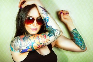 Piękna dziewczyna ze stylowym makijażem i wytatuowanymi ramionami .. \ t