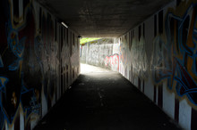 Foot Tunnel In A City With Graffiti On The Walls