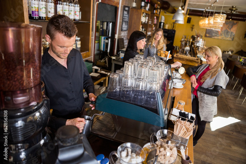 Fotografie, Obraz  Bartender Working At Counter While Female Colleague Serving Coff