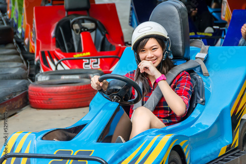 Staande foto Amusementspark Cute Thai girl is driving Go-kart from the starting point