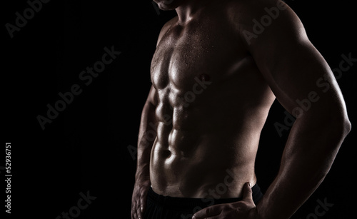 Fotografía  Close up of perfect male body isolated on black background