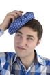 Junger Mann im karrierten Hemd hat Kopfschmerzen