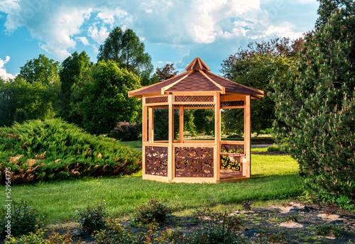 Fotografia Outdoor wooden gazebo over summer landscape background