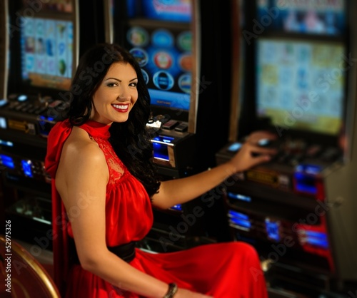 Spoed Foto op Canvas Muziekwinkel Beautiful woman in red dress playing slot machine